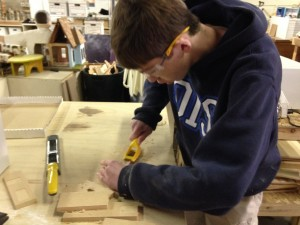 Ben working on a bird house based on his own home